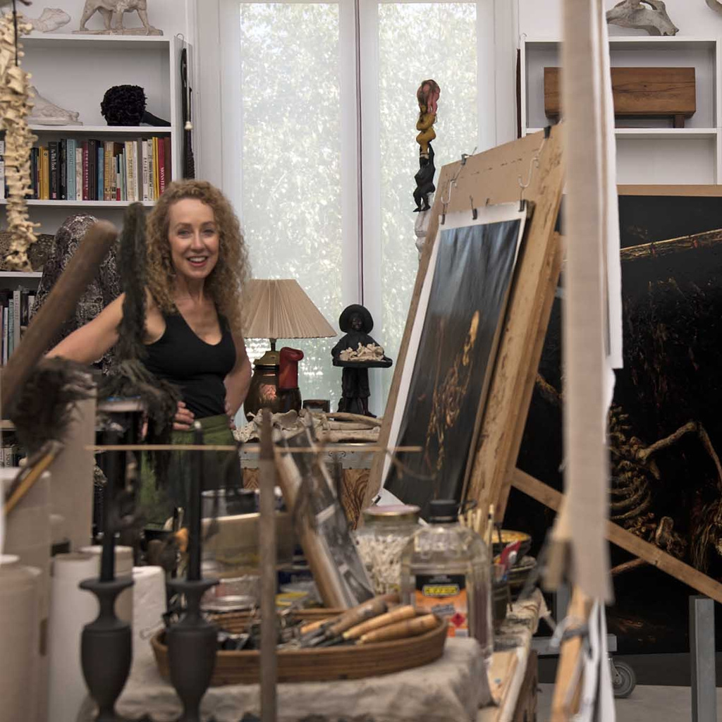 Terry Taylor looking across in her studio as she paints one of her work